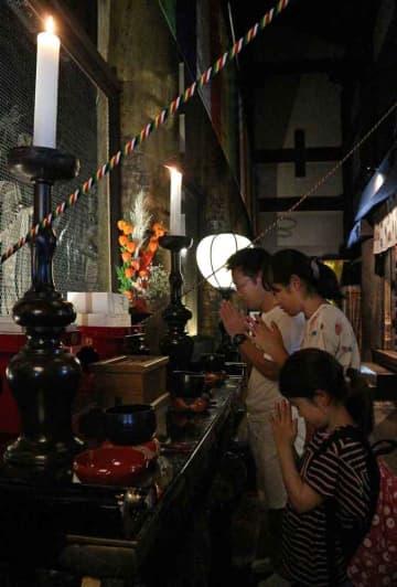 本堂の内陣で静かに手を合わせる参拝者(京都市東山区・清水寺)
