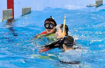 訓練用プールで救助されるシュノーケリング初心者(中央)。波と風を起こすと、救命胴衣なしでは浮かぶことが難しくなった=横浜海上防災基地
