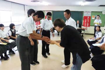 ホストファミリーにあいさつする長野県木曽町の中学生(左)=福島公民館