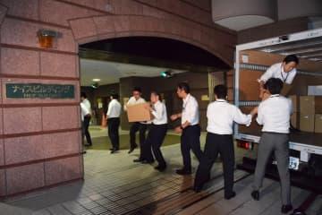 すてきナイスグループ本社の家宅捜索で押収した資料を運び出す捜査員ら=5月16日、横浜市鶴見区