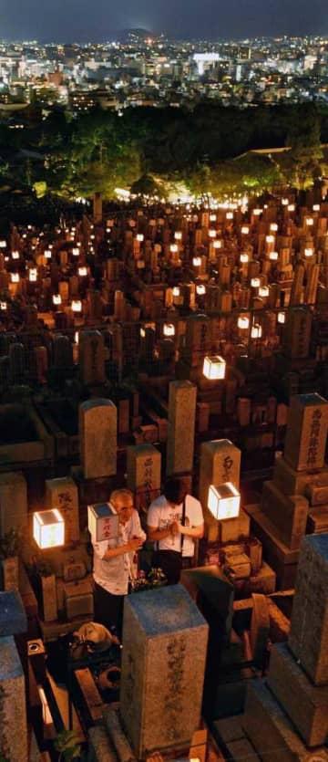 提灯がともる墓前で手を合わせる参拝者(14日午後7時46分、京都市東山区・大谷祖廟)