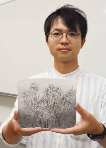 石こう版画を作るワークショップへの参加を呼び掛ける米村太一特任助教=佐賀市の佐賀大学