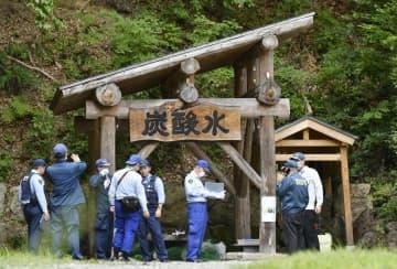 男女2人が倒れていた井戸の周辺を調べる福島県警の捜査員=15日午後、福島県金山町