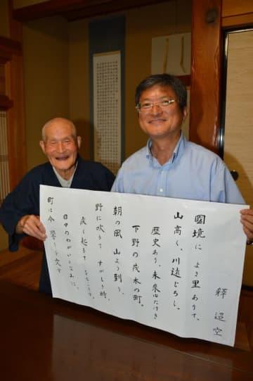 書き上げられた歌詞の美しい墨字を持つ中村豊さん(左)と強さん