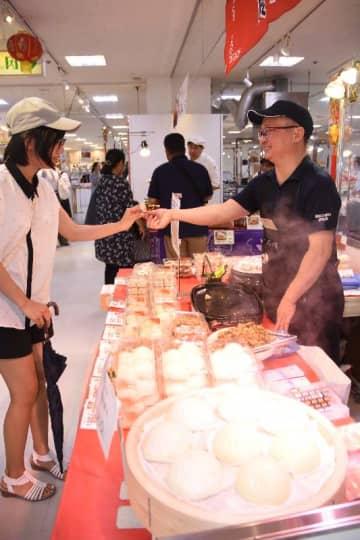 中華まんや海老ニラまんなどが並ぶ店内で試食をする来場者=16日、那覇市のデパートリウボウ