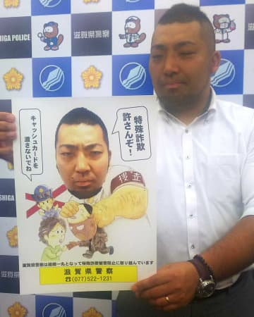 自身を起用したポスターを手にするモデルの刑事(大津市・滋賀県警本部)
