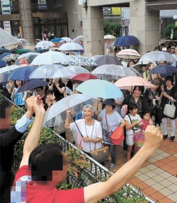 台風接近で雨が降る中、集まった支持者に両手を掲げてアピールする候補者=16日午後2時10分ごろ、仙台市泉区