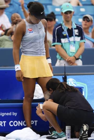 女子シングルス準々決勝で治療を受ける大坂なおみ。第3セットで途中棄権した=シンシナティ(共同)