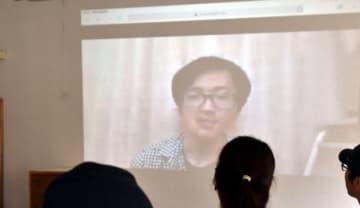東京の会場からライブ配信した発起人の小幡和輝さんのメッセージに耳を傾ける盛岡会場の参加者