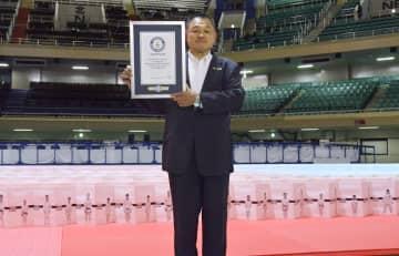 ギネス世界記録に認定されたポスターの前で記念写真に納まる全柔連の山下泰裕会長=21日、日本武道館