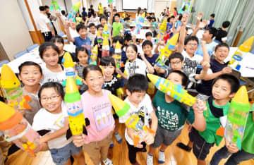 ペットボトルロケットの完成を喜ぶ児童たち=8月22日、福井県あわら市の福井県立芦原青年の家