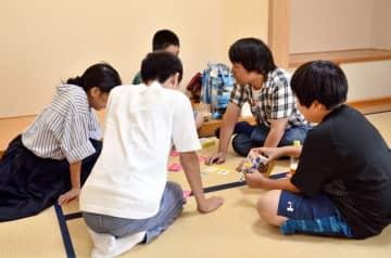 カードゲームで交流する子どもや支援者たち=佐賀市松原の佐賀バルーンミュージアム