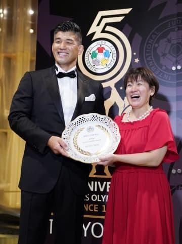 国際柔道連盟から表彰を受け、笑顔で記念写真に納まる井上康生氏(左)と谷亮子さん=23日夜、東京都内のホテル
