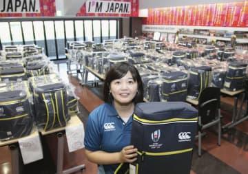 ラグビー・ワールドカップ日本大会中に着用するユニホームなどを受け取ったボランティアの女性=24日午後、埼玉県熊谷市の県営熊谷ラグビー場