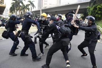 警官隊(左の2人)と衝突する若者ら=24日、香港・九竜地区(共同)