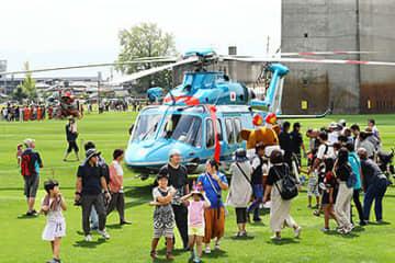 初参加の県警ヘリ「つるぎ」などが展示され、大勢の来場者でにぎわう会場=クロスランドおやべ