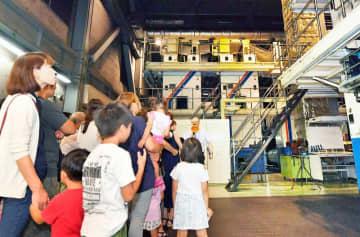 巨大な輪転機を見学する親子連れら=8月25日、福井県福井市の福井新聞社