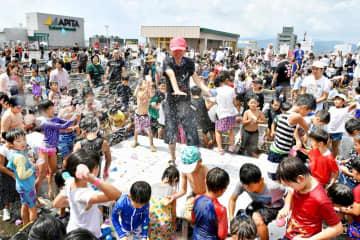 歓声を上げ、4万個の水風船を投げ合う子どもたち=8月25日、福井県福井市のエルパ屋上