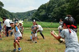 水鉄砲で水を飛ばし合う児童ら=神戸市北区山田町藍那
