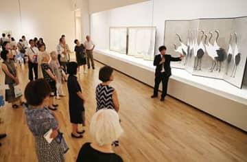 八木学芸課長(右)の解説を聞きながら、加山又造の「群鶴図」に見入る招待客=県美術館
