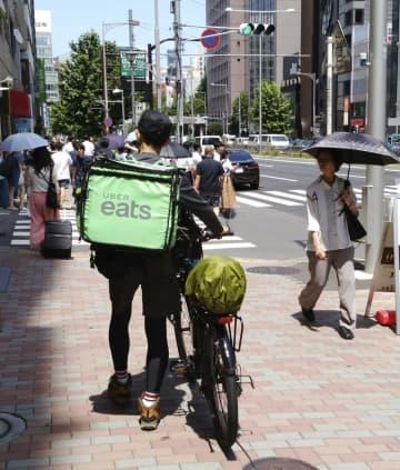 「ウーバーイーツ」の配達員=6月、東京都内