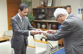 菊谷市長に善意を手渡す今井社長(左)