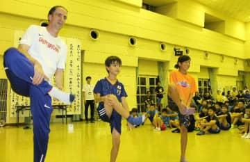 児童らにウオーミングアップの方法を指導するサッチャーさん(左)。中央は長男の奏信君=中津市の三光公民館