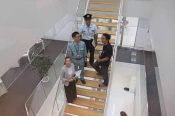 吹き抜け階段の構造確認や防火指導を行う市消防局員ら(京都市伏見区・クロスエフェクト)