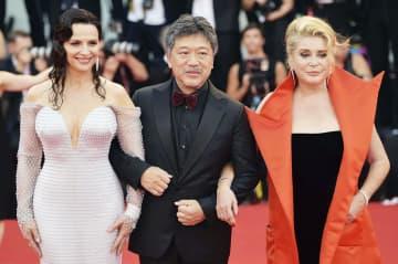 第76回ベネチア国際映画祭でレッドカーペットを歩く(左から)ジュリエット・ビノシュさん、是枝裕和監督、カトリーヌ・ドヌーブさん=28日、イタリア・ベネチア(ゲッティ=共同)