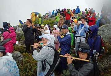 雨の中、日の出の方角に向け登山囃子を奏でる参拝者=30日午前5時7分、岩木山山頂