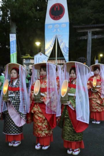 「八咫の火祭り」で竹灯籠を手に練り歩く平安装束姿の女性ら=31日午後、和歌山県田辺市