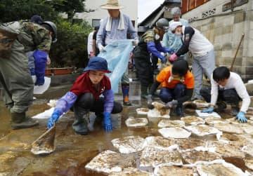 吸着マットを使い流出油を除去する被災者の同僚や自衛隊員=31日午後、佐賀県大町町