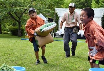 ニホンザルの餌が入った約10キロの袋を精いっぱい運ぶ子ども