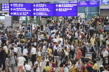 デモの影響で空港と市内を結ぶ列車の運行が乱れ、混雑する香港国際空港の到着ロビー=1日(共同)