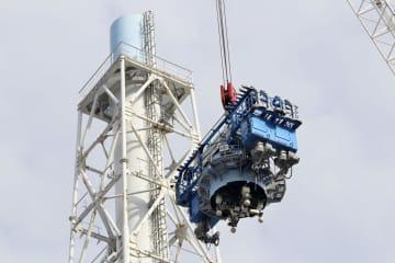 切断されて大型クレーンで下ろされる福島第1原発1、2号機共用排気筒の最上端部(装置中央の円筒のもの)=1日午後(東京電力提供)