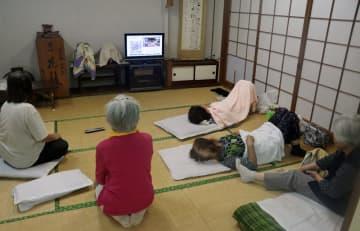 避難所で、大雨の被害を伝えるテレビを見る地元住民。多くの住民は「行かない」という選択をした=28日午前9時55分、佐世保市江迎町の江迎地区公民館