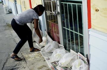 1日、バハマでハリケーン上陸に備え店舗入り口に土のうを置く女性(AP=共同)