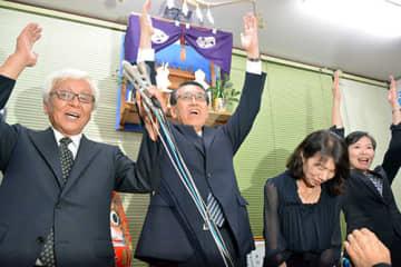 万歳をして再選を喜ぶ丸山至氏(中央)=酒田市松原南の選挙事務所