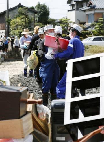 浸水被害を受けた佐賀県大町町の住宅から、家財道具をリレーして運び出すボランティアら=3日午後