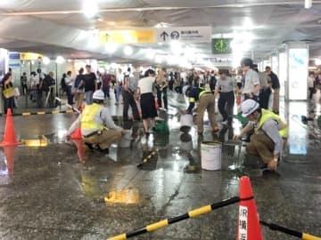 構内にあふれ出た水を処理する駅員ら=3日午後8時ごろ、横浜市西区の横浜駅