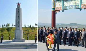 4日付の労働新聞に掲載された、中国義勇軍兵士らの陵墓(写真左)を訪れる中国の王毅国務委員兼外相(写真右の右から4人目)の写真(コリアメディア提供・共同)