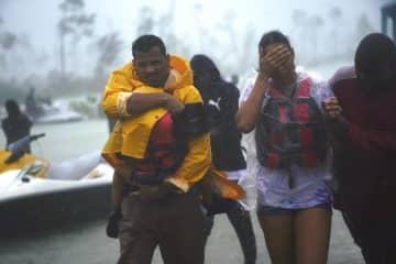 ハリケーン「ドリアン」に伴う雨が続く中、救助され安全な場所へと向かう家族=3日、バハマ(AP=共同)