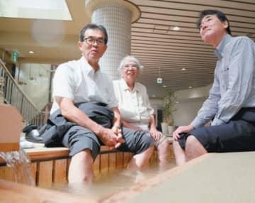 新装トキハ別府店がプレオープン。地下1階に設けられた足湯を楽しむ人たち=5日午前、別府市