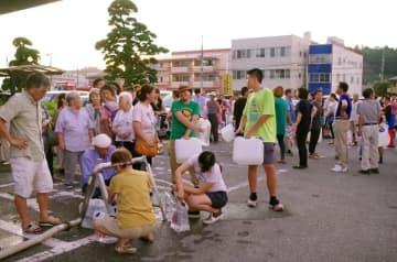 生活用水と飲み水の配給が行われ、ポリタンクなどを手にした市民が長蛇の列を作った=9日夕、東金市役所