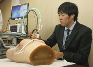 乳がんを可視化し発見する検査装置の実演をする神戸大の木村建次郎教授=13日午後、神戸市