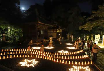 中秋の名月が空に浮かぶ中、ともしびに彩られた境内を歩く参拝者たち(13日午後7時30分、大津市石山寺1丁目・石山寺)