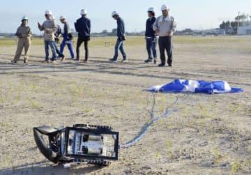 パラシュートを使い約100メートル上空から降下したロボット=15日午後、福島県南相馬市