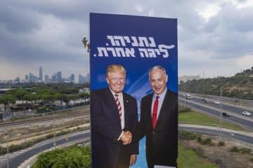 イスラエルのネタニヤフ首相(右)とトランプ米大統領が写った選挙の看板=8日、イスラエル・テルアビブ(AP=共同)