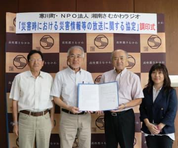 協定を結んだ木村俊雄寒川町長(中央右)と今井静二湘南さむかわラジオ理事長(同左)=寒川町