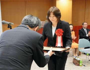 厚生労働大臣表彰状を受け取る水上村の担当者(右)=10日、熊本市東区